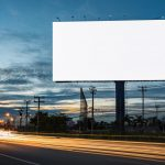 A blank billboard in the highway at night