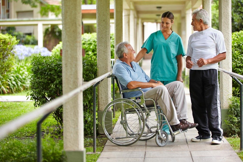 two seniors talking to a nurse in the garden