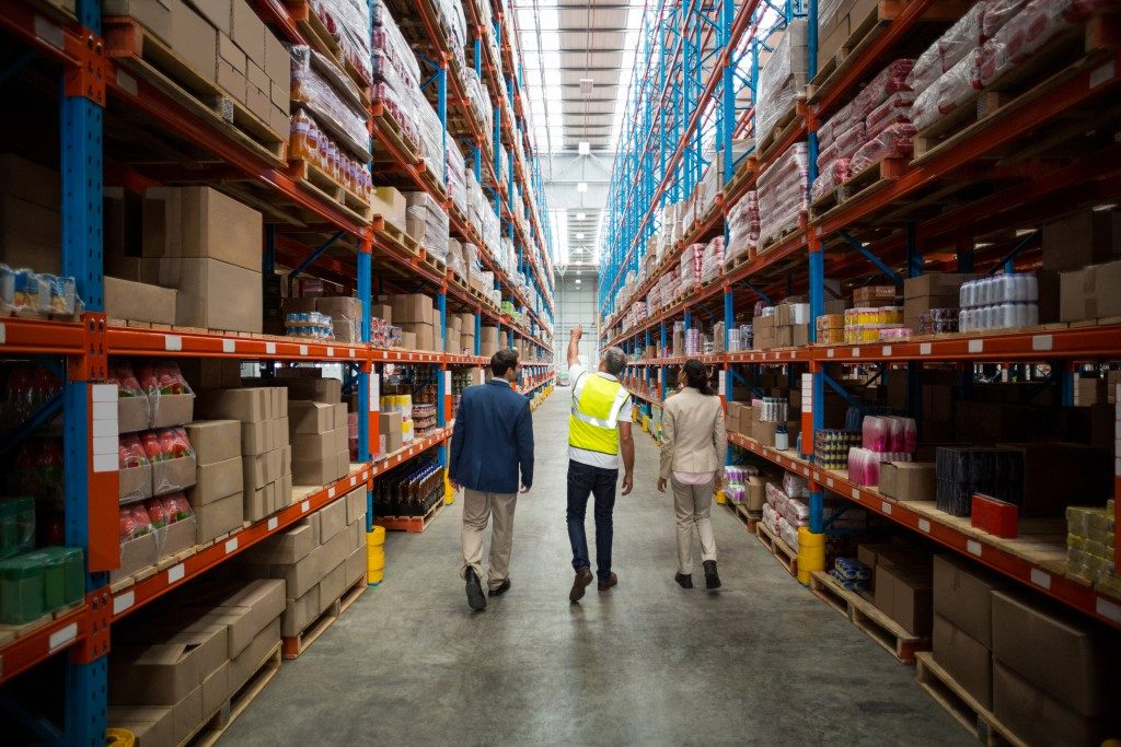 people monitoring the cargo inside the warehouse