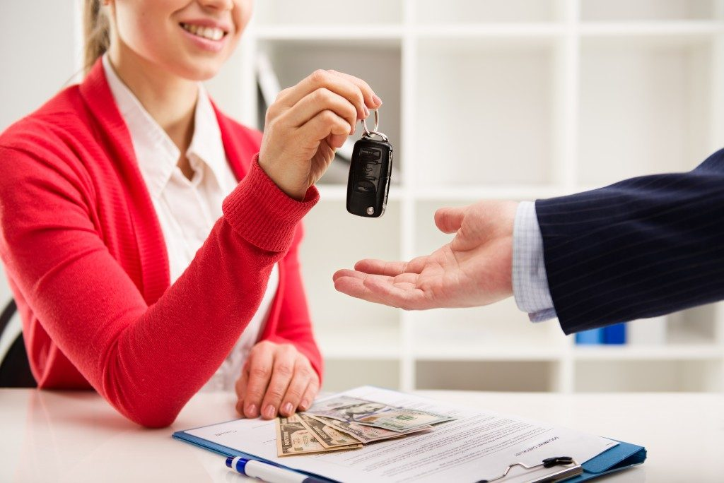 Woman giving car keys to buyer