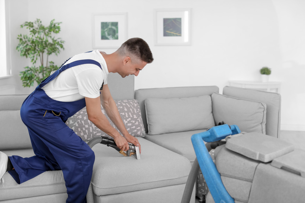 man cleaning the sofa