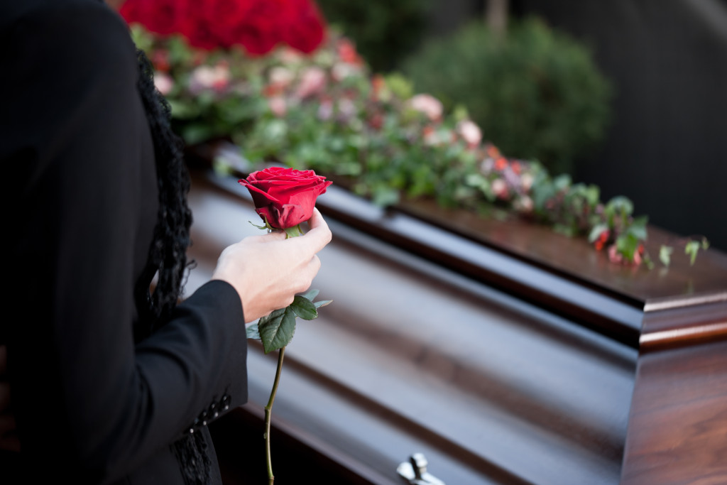 woman laying rose on coffin